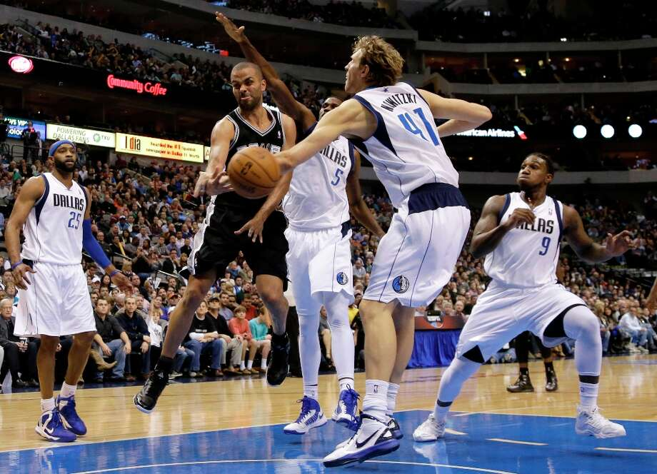 The Spurs' Tony Parker (second from left) passes the ball from beneath the basket as Dallas Mavericks' Dirk Nowitzki (41) defends in the second half  on Friday, Jan. 25, 2013, in Dallas. Mavericks' Vince Carter (25), Bernard James (5) and Jae Crowder (9) help on the play in the 113-107 Spurs win. Photo: Tony Gutierrez, Associated Press / AP