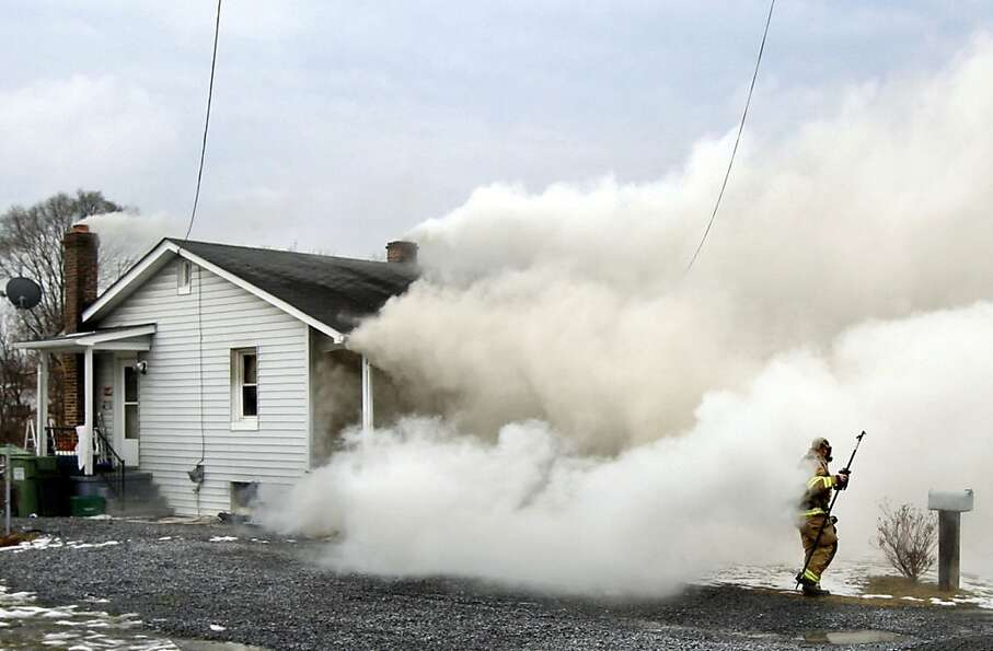A firefighter works to battle a house fire on Monday, Jan. 28, 2013, in Stephenson, Va. (AP Photo/Th