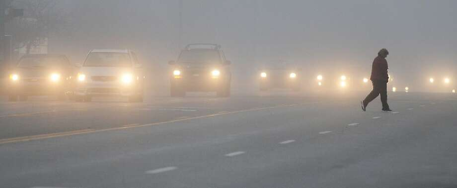 A pedestrian crosses a street as a blanket of fog covers the city early Monday, Jan. 28,  2013, in Salina, Kan. (AP Photo/Salina Journal, Tom Dorsey) Photo: Tom Dorsey, Associated Press