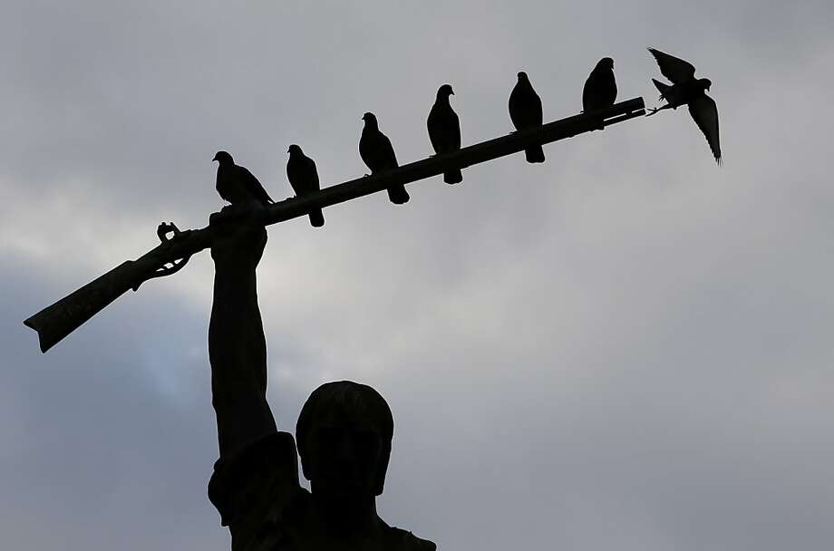 Birds roost on the rifle portion of a Benjamin  Milam statute at dusk, Monday, Jan. 28, 2013, in San Antonio, Texas. Milam was leading figure in the Texas Revolution. (AP Photo/Eric Gay) Photo: Eric Gay, Associated Press