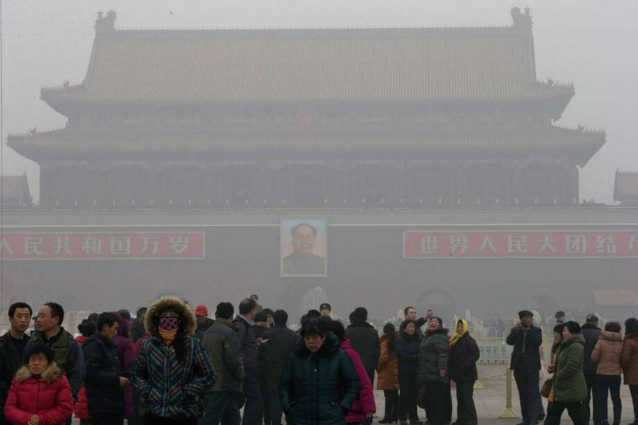 Visitors stand on Tiananmen Square across from a portrait of former Chinese leader Mao Zedong in thick haze in Beijing Tuesday, Jan. 29, 2013. Extremely high pollution levels shrouded eastern China for the second time in about two weeks Tuesday, forcing airlines in Beijing and elsewhere to cancel flights because of poor visibility and prompting government warnings for residents to stay indoors. Photo: Ng Han Guan