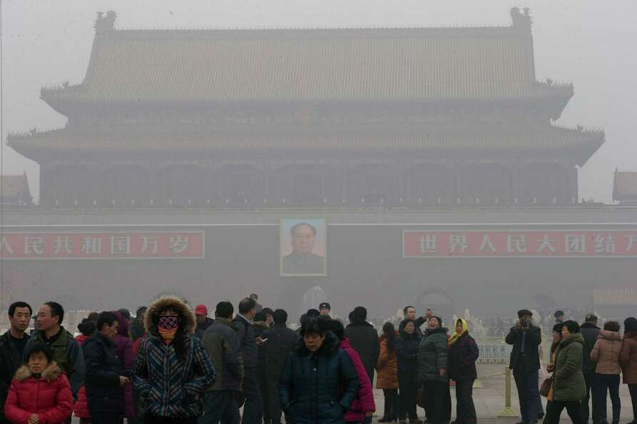 Visitors stand on Tiananmen Square across from a portrait of former Chinese leader Mao Zedong in thi