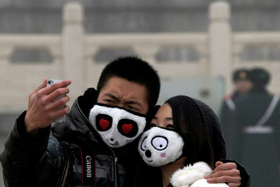 A couple wearing protective masks poses for a self portrait in thick haze on Tiananmen Square in Beijing Tuesday, Jan. 29, 2013. Extremely high pollution levels shrouded eastern China for the second time in about two weeks Tuesday, forcing airlines in Beijing and elsewhere to cancel flights because of poor visibility and prompting government warnings for residents to stay indoors. Photo: Ng Han Guan