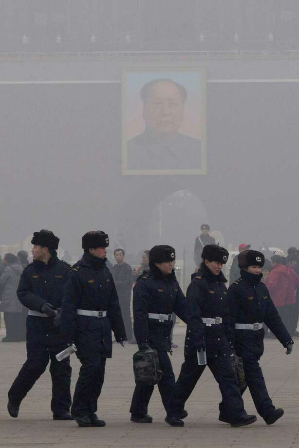 Chinese security personnel march in thick haze near the portrait of former Chinese leader Mao Zedong in Beijing Tuesday, Jan. 29, 2013. Extremely high pollution levels shrouded eastern China for the second time in about two weeks Tuesday, forcing airlines in Beijing and elsewhere to cancel flights because of poor visibility and prompting government warnings for residents to stay indoors. Photo: Ng Han Guan