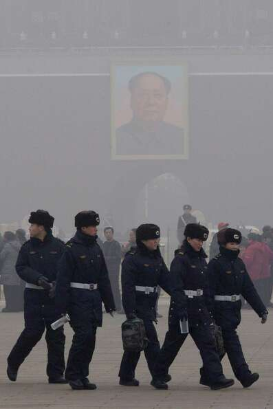 Chinese security personnel march in thick haze near the portrait of former Chinese leader Mao Zedong