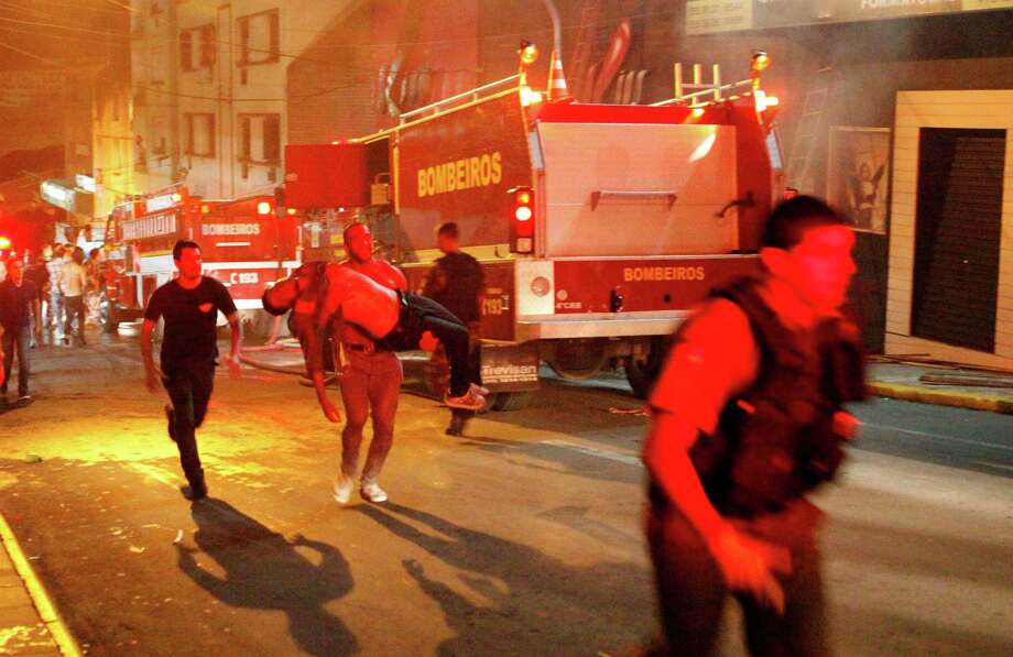 A man carries an injured man, victim of a fire at the Kiss  club in Santa Maria city,  Rio Grande do Sul state, Brazil, early Sunday, Jan. 27, 2013.  Firefighters say that the death toll from a fire that swept through a crowded nightclub in southern Brazil has risen to 180. Officials say the fire broke out  while a band was performing. At least 200 people have been injured. Photo: Agencia RBS