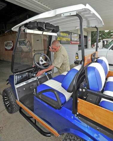 George Murray, a Nederland resident owns this tricked out 2004 Club Car DS. He even pulls a custom made trailer behind it. The seats are color matched to the body paint as well as the trailer. Seen above his head is the two speaker stereo system.  The culture of golf carts. People love to drive them in places other then just golf courses. Many people actually know you have to have a driver's license to operate it, but, do they know about all the laws pertaining to the golf carts, for instance, you could get a DWI while driving one.  Dave Ryan/The Enterprise