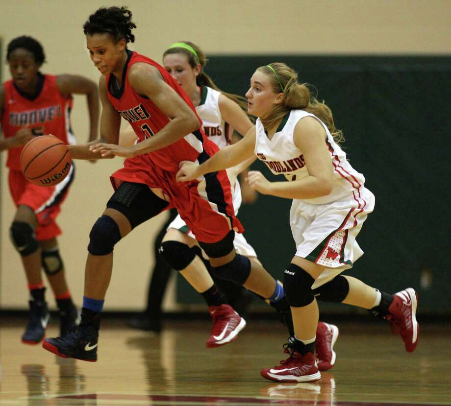 Manvel's Brianna Turner (left) dribbles the ball up court past The Woodlands' Katie Burke during the first half of a high school basketball game, Tuesday, December 4, 2012 at The Woodlands High School. Photo: Eric Christian Smith, Freelance
