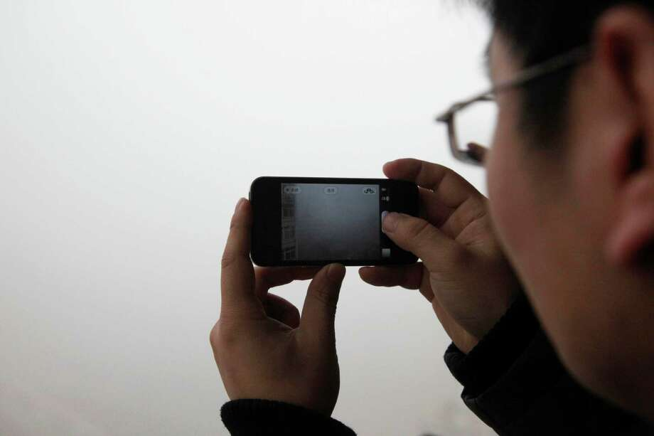 A man takes a picture with his mobile phone of the heavy smog in Qingdao, east China's Shandong province on January 29, 2013.  Residents across northern China battled through choking pollution on January 29, as air quality levels rose above index limits in Beijing amid warnings that the smog may not clear until January 31. Photo: STR, AFP/Getty Images / AFP