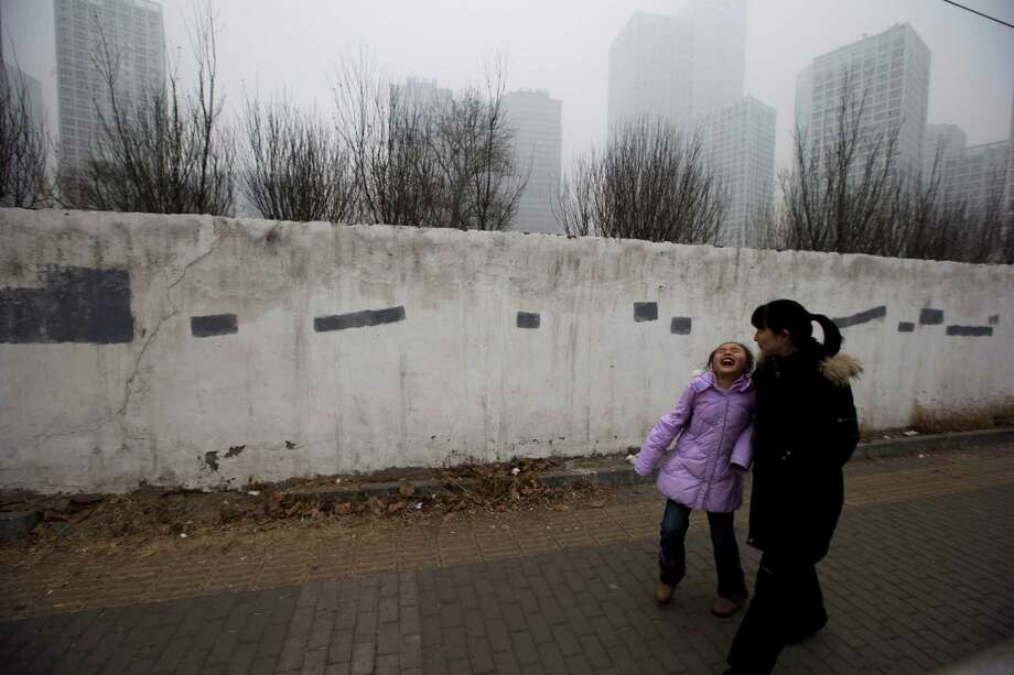 A child laughs as she passes by a smog-shrouded residential district in Beijing Tuesday, Jan. 29, 2013. Extremely high pollution levels shrouded eastern China for the second time in about two weeks Tuesday, forcing airlines in Beijing and elsewhere to cancel flights because of poor visibility and prompting government warnings for residents to stay indoors. Photo: Ng Han Guan, Associated Press / AP