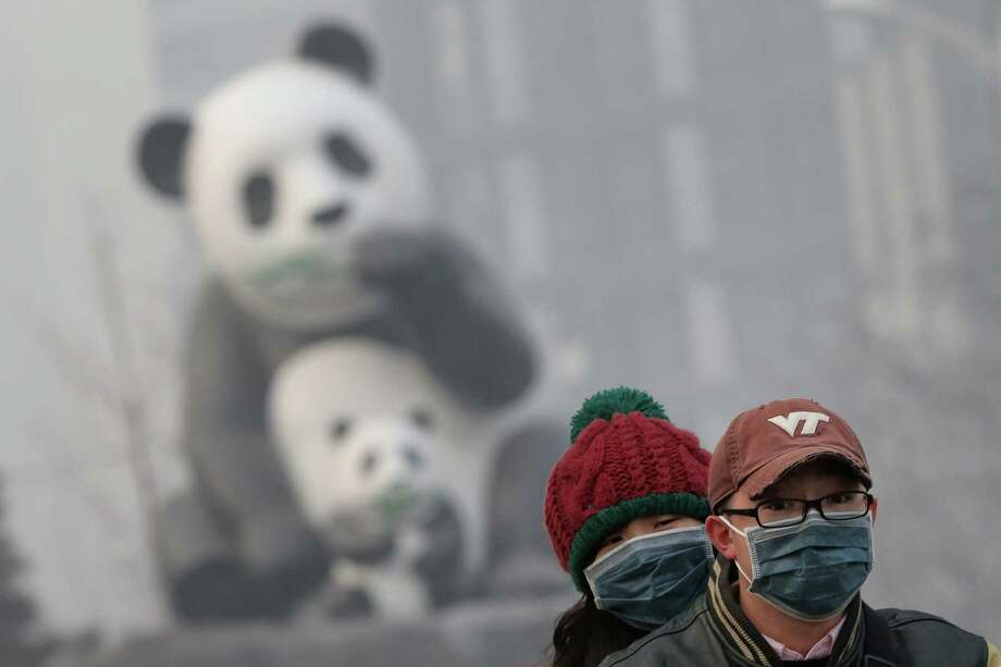 Beijing residents wearing the masks ride a motorcycle through a panda sculpture during severe pollution on January 23, 2013 in Beijing, China. The air quality in Beijing on Wednesday hit serious levels again, as smog blanketed the city. Photo: Feng Li, Getty Images / 2013 Getty Images