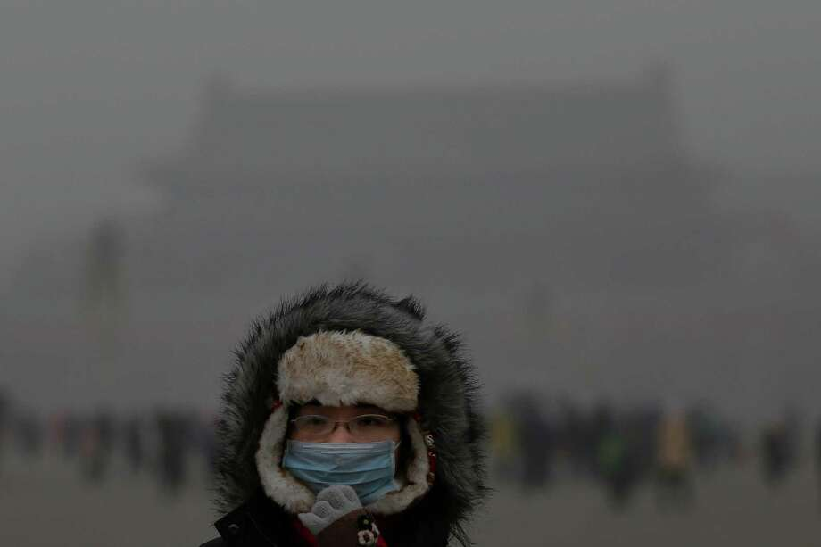 A tourist wearing the mask visits the Tiananmen Square at dangerous levels of air pollution on January 23, 2013 in Beijing, China. The air quality in Beijing on Wednesday hit serious levels again, as smog blanketed the city. Photo: Feng Li, Getty Images / 2013 Getty Images
