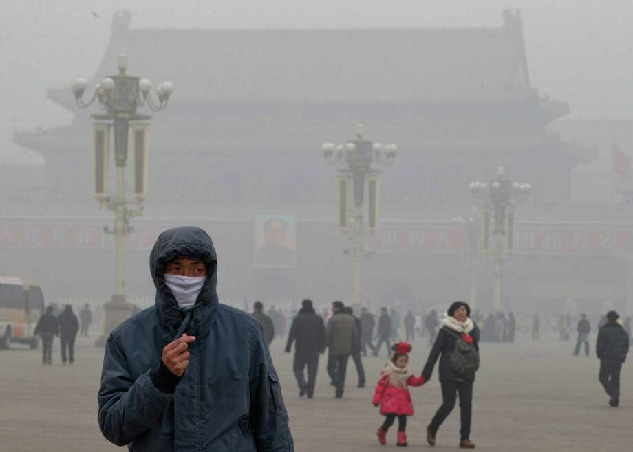 A man wears a mask on Tiananmen Square in thick haze in Beijing Tuesday, Jan. 29, 2013. Extremely high pollution levels shrouded eastern China for the second time in about two weeks Tuesday, forcing airlines in Beijing and elsewhere to cancel flights because of poor visibility and prompting government warnings for residents to stay indoors. Photo: Ng Han Guan, Associated Press / AP