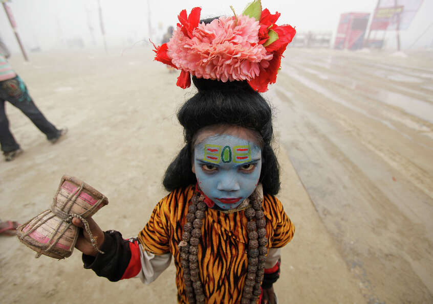 An Indian child dressed as Hindu god Shiva to seek alms reacts to camera at Sangam, the confluence o