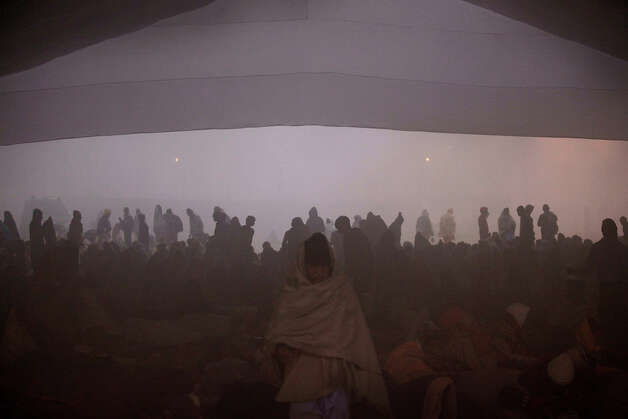 Hindu devotees take shelter in a make shift hanger after arriving at Sangam, the confluence of the Ganges, Yamuna and mythical Saraswati river, ahead of the Maha Kumbh festival in Allahabad, India, Sunday Jan. 13, 2013. Millions of Hindu pilgrims are expected to take part in the large religious congregation of a period of over a month on the banks of Sangam, which falls every 12 years.  (AP Photo/Manish Swarup) Photo: Manish Swarup, ASSOCIATED PRESS / AP2013