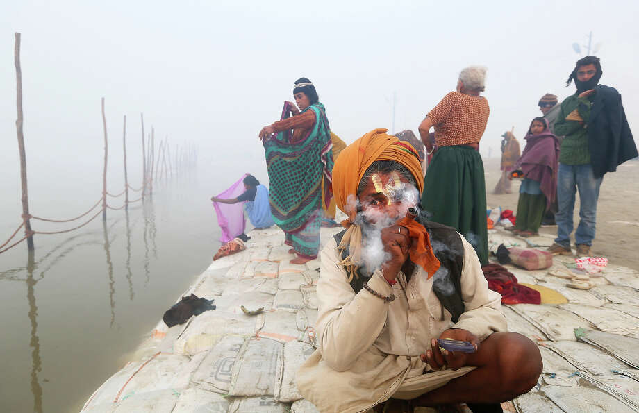 An Indian holy man smokes as others get ready for a dip amidst morning fog, at Sangam, the confluence of the rivers Ganges, Yamuna and mythical Saraswati, ahead of the Maha Kumbh festival in Allahabad, India, Saturday, Jan. 12, 2013. Millions of Hindu pilgrims are expected to take part in the large religious congregation of a period of over a month on the banks of Sangam during the Maha Kumbh festival in January 2013, which falls every 12th year. (AP Photo /Manish Swarup) Photo: Manish Swarup, ASSOCIATED PRESS / AP2013