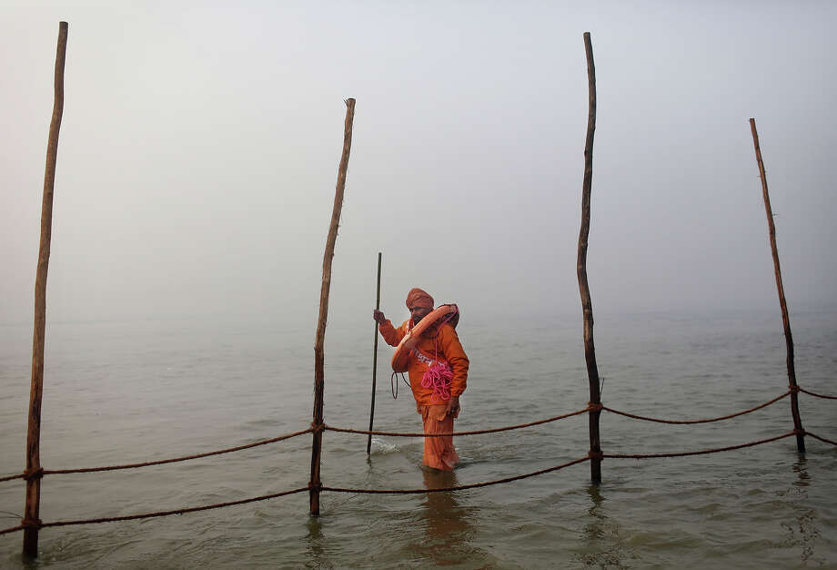 An Indian Hindu volunteer carries a life preserver as he watches the fence line in the bathing area at Sangam, the confluence of the rivers Ganges, Yamuna and mythical Saraswati, during the royal bath on Makar Sankranti at the start of the Maha Kumbh Mela in Allahabad, India, Monday, Jan. 14, 2013. Millions of Hindu pilgrims are expected to take part in the large religious congregation that lasts more than 50 days on the banks of Sangam during the Maha Kumbh Mela in January 2013, which falls every 12th year. (AP Photo/Kevin Frayer) Photo: Kevin Frayer, ASSOCIATED PRESS / AP2013