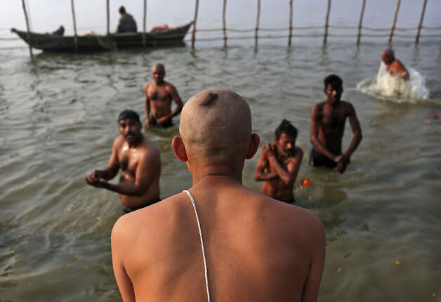 Indian Hindu pilgrims, some with shaved heads, take a dip at Sangam, the confluence of the rivers Ganges, Yamuna and mythical Saraswati, ahead of the Maha Kumbh Mela in Allahabad, India, Sunday Jan. 13, 2013. Millions of Hindu pilgrims are expected to take part in the large religious congregation of a period of over a month on the banks of Sangam during the Maha Kumbh Mela in January 2013, which falls every 12th year. (AP Photo/Kevin Frayer) Photo: Kevin Frayer, ASSOCIATED PRESS / AP2013