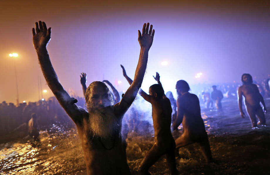 EDS NOTE; NUDITY - Indian Hindu holy men, or Naga Sadhus, celebrate in the water at Sangam, the confluence of the rivers Ganges, Yamuna and mythical Saraswati, during the royal bath on Makar Sankranti at the start of the Maha Kumbh Mela in Allahabad, India, Monday, Jan. 14, 2013. Millions of Hindu pilgrims are expected to take part in the large religious congregation that lasts more than 50 days on the banks of Sangam during the Maha Kumbh Mela in January 2013, which falls every 12th year. (AP Photo/Kevin Frayer) Photo: Kevin Frayer, ASSOCIATED PRESS / AP2013