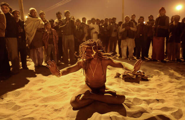An Indian Hindu holy man, or Naga Sadhu,performs naked following an evening prayer ceremony at Sangam, the confluence of the holy rivers Ganges and Yamuna and mythical Saraswati at the Maha Kumbh Mela in Allahabad, India, Tuesday, Jan. 15, 2013. Millions of Hindu pilgrims are expected to take part in the large religious congregation that lasts more than 50 days on the banks of Sangam during the Maha Kumbh Mela in January 2013, which falls every 12th year. (AP Photo/Kevin Frayer) Photo: Kevin Frayer, ASSOCIATED PRESS / AP2013