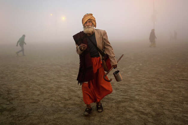 An Indian Hindu holy man, or Sadhu, walks before taking a bath at Sangam, the confluence of the rivers Ganges, Yamuna and mythical Saraswati, ahead of the Maha Kumbh Mela in Allahabad, India, Sunday Jan. 13, 2013. Millions of Hindu pilgrims are expected to take part in the large religious congregation of a period of over a month on the banks of Sangam during the Maha Kumbh Mela in January 2013, which falls every 12th year. (AP Photo/Kevin Frayer) Photo: Kevin Frayer, ASSOCIATED PRESS / AP2013
