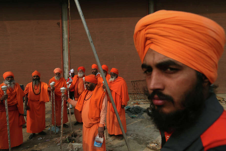 An Indian Sikh walks past a group of Indian holy men waiting to participate in a religious processio