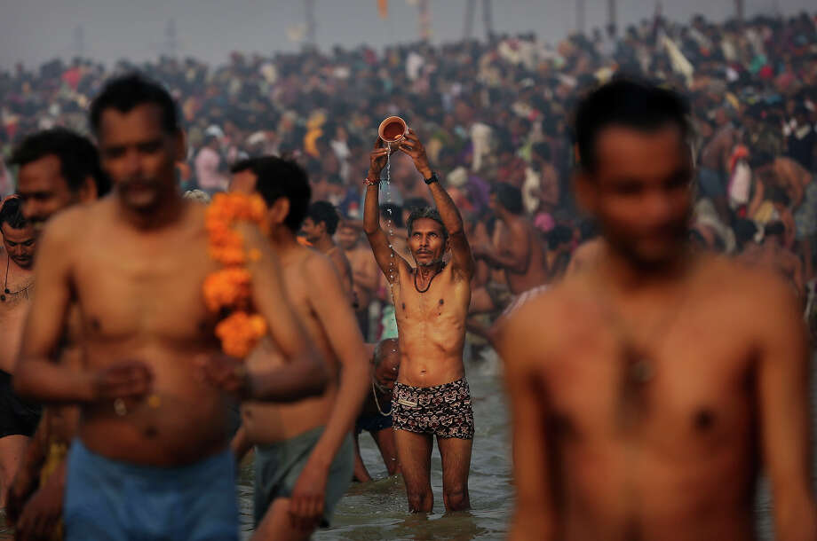 Indian Hindu devotees pray at Sangam, the confluence of the rivers Ganges, Yamuna and mythical Saraswati, during the royal bath on Makar Sankranti at the start of the Maha Kumbh Mela in Allahabad, India, Monday, Jan. 14, 2013. Millions of Hindu pilgrims are expected to take part in the large religious congregation that lasts more than 50 days on the banks of Sangam during the Maha Kumbh Mela in January 2013, which falls every 12th year. (AP Photo/Kevin Frayer) Photo: Kevin Frayer, ASSOCIATED PRESS / AP2013