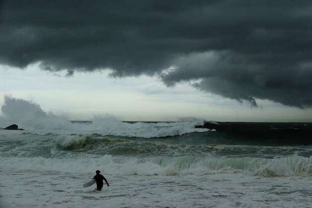 A surfer leaves the water as storm clouds gather at Coogee Beach.   Photo: Mark Metcalfe, Getty / 2013 Getty Images