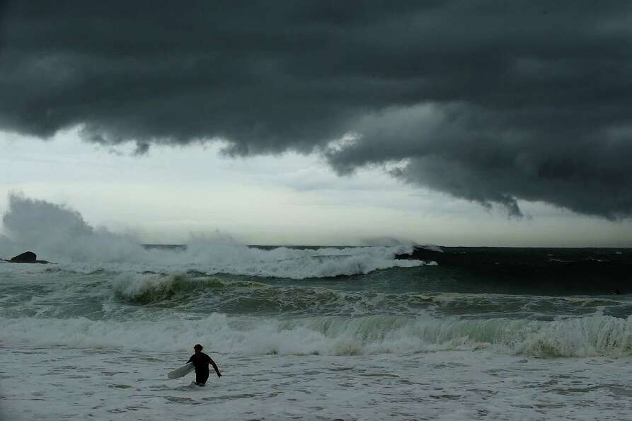 A surfer leaves the water as storm clouds gather at Coogee Beach.