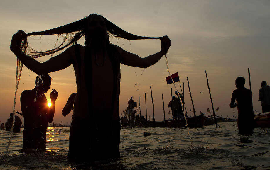"A Hindu devotee takes a holy bath at ""Sangam,"" the meeting point of Indian holy rivers of Ganges, Yamuna and the mythical Saraswati, on occasion of ""Paush Purnima,"" considered to be very auspicious according to Hindu calendars, during the Maha Kumbh festival in Allahabad, India, Sunday, Jan. 27, 2013. Hundreds of thousands of Hindu pilgrims are expected to take a ritual dip at Sangam on Sunday. Millions of Hindu pilgrims are likely to attend the Maha Kumbh festival, which is one of the world's largest religious gatherings that lasts 55 days and falls every 12 years. (AP Photo/Rajesh Kumar Singh) Photo: Rajesh Kumar Singh, ASSOCIATED PRESS / AP2013"