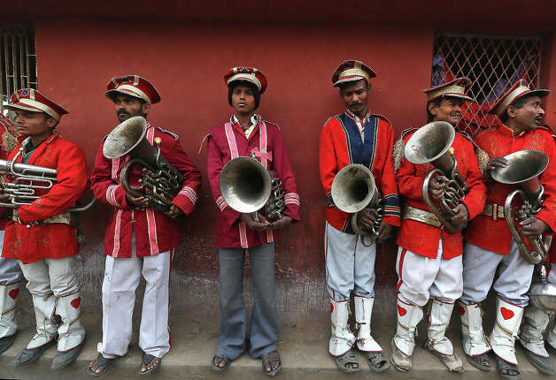 Members of an brass band wait for a religious procession to start towards the Sangam, the confluence of the rivers Ganges, Yamuna and mythical Saraswati, ahead of the Maha Kumbh festival in Allahabad, India, Saturday, Jan. 12, 2013. Millions of Hindu pilgrims are expected to take part in the large religious congregation of a period of over a month on the banks of Sangam during the Maha Kumbh festival in January 2013, which falls every 12th year. (AP Photo /Manish Swarup) Photo: Manish Swarup, ASSOCIATED PRESS / AP2013