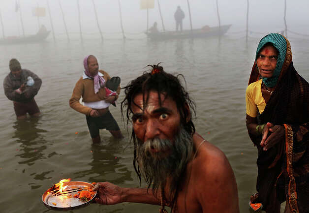 An Indian Hindu holy man performs morning prayers for devotees at Sangam, the confluence of the holy rivers Ganges and Yamuna and mythical Saraswati at the Maha Kumbh Mela in Allahabad, India, Tuesday, Jan. 15, 2013. Millions of Hindu pilgrims are expected to take part in the large religious congregation that lasts more than 50 days on the banks of Sangam during the Maha Kumbh Mela in January 2013, which falls every 12th year. (AP Photo/Kevin Frayer) Photo: Kevin Frayer, ASSOCIATED PRESS / AP2013