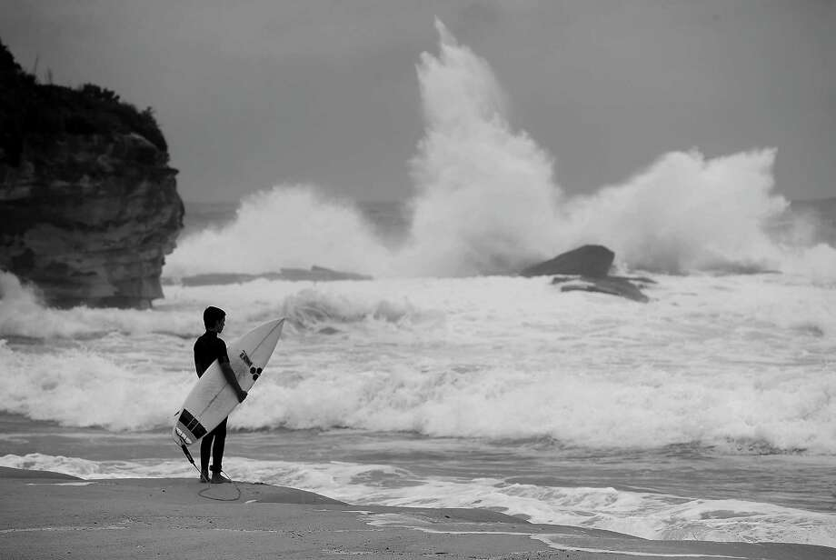 A surfer waits to jump in to the ocean during stormy conditions at Coogee Beach.  Photo: Mark Metcalfe, Getty / 2013 Getty Images