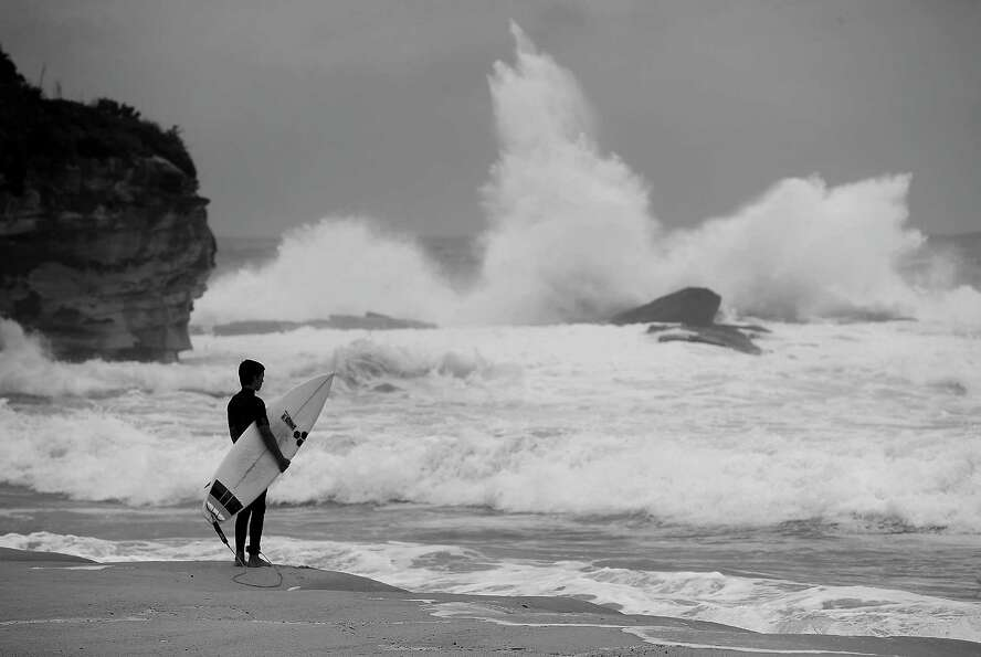 A surfer waits to jump in to the ocean during stormy conditions at Coogee Beach.