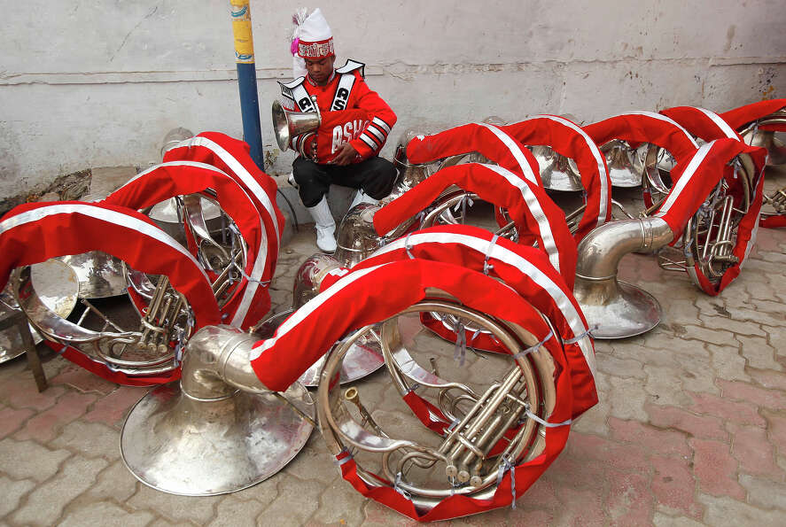 An Indian brass band members checks his instrument  before the start of a religious procession towar