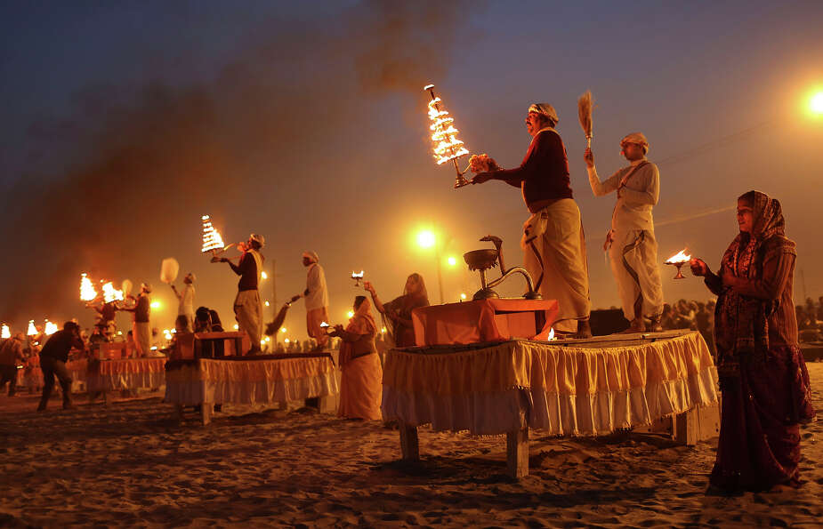 Indian Hindu priests and a devotees take part in an evening prayer ritual known as Arti, at Sangam,