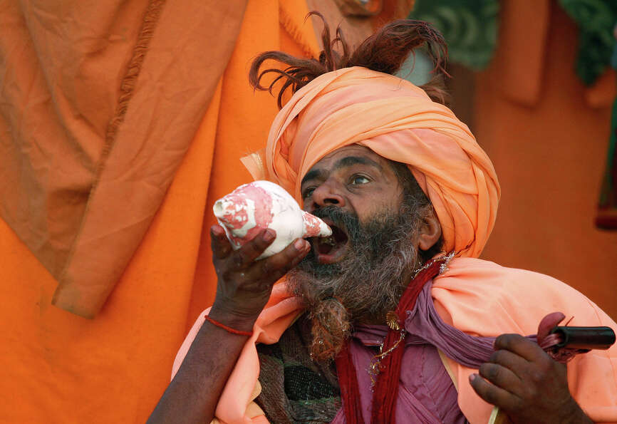 A Hindu holy man drinks the river Ganges' water at Sangam, the confluence of rivers Ganges, Yamuna a