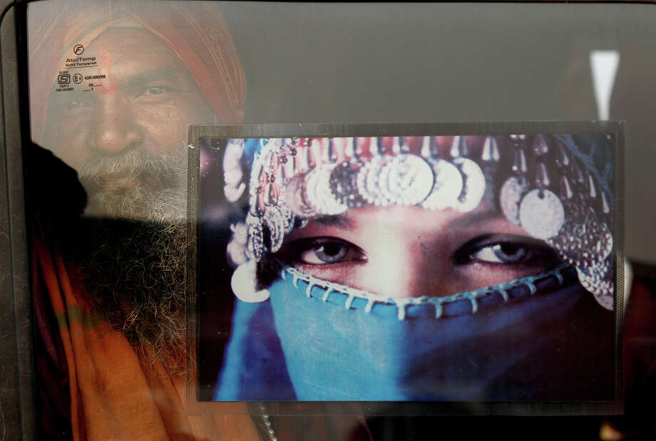 A Hindu holy man looks out from a window of his car as he arrives at Sangam, the confluence of rivers Ganges, Yamuna and mythical Saraswati, ahead of the Maha Kumbh Mela, in Allahabad, india, Sunday, Jan. 13, 2013. Millions of Hindu pilgrims are expected to take part in the large religious congregation of a period of over a month on the banks of Sangam during the Maha Kumbh festival in January 2013, which falls every 12th year. (AP Photo/Rajesh Kumar Singh) Photo: Rajesh Kumar Singh, ASSOCIATED PRESS / AP2013