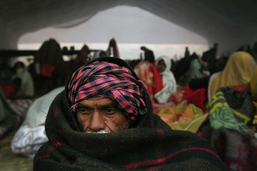 A Hindu devotees takes shelter in a make shift hanger after arriving at Sangam, the confluence of th