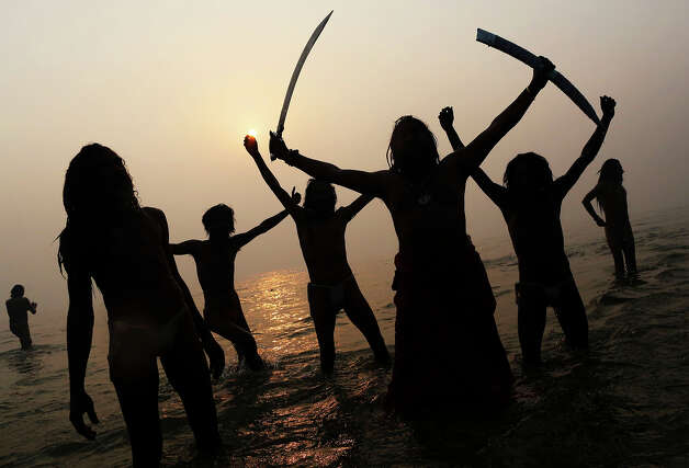 Indian Hindu holy men, or Sadhus, are silhouetted as they celebrate in the water at Sangam, the confluence of the rivers Ganges, Yamuna and mythical Saraswati, during the royal bath on Makar Sankranti at the start of the Maha Kumbh Mela in Allahabad, India, Monday, Jan. 14, 2013. Millions of Hindu pilgrims are expected to take part in the large religious congregation that lasts more than 50 days on the banks of Sangam during the Maha Kumbh Mela in January 2013, which falls every 12th year. (AP Photo/Kevin Frayer) Photo: Kevin Frayer, ASSOCIATED PRESS / AP2013