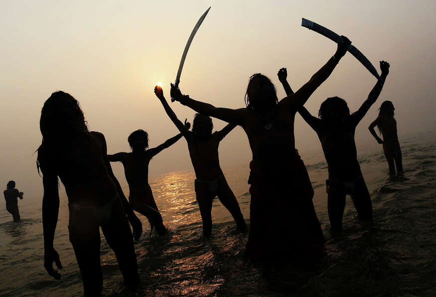 Indian Hindu holy men, or Sadhus, are silhouetted as they celebrate in the water at Sangam, the conf