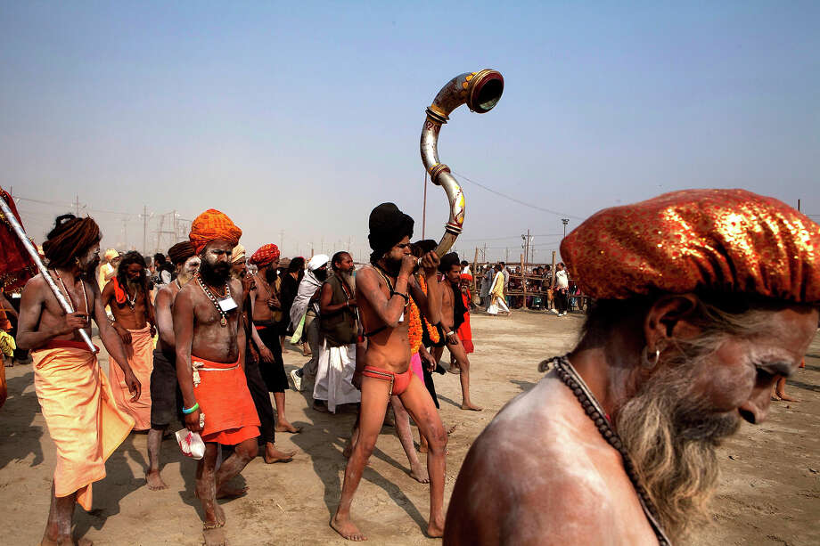 Indian holy men move in a procession towards  Sangam, the confluence of the Rivers Ganges, Yamuna and mythical Saraswati as others cross a make shift bridge,  ofor a holy dip n one of the most auspicious day Makar Sankranti,  the first day of the Maha Kumbh Mela, in Allahabad, India, Monday, Jan. 14, 2013. Millions of Hindu pilgrims are expected to take part in the large religious congregation of a period of over a month on the banks of Sangam during the Maha Kumbh Mela in January 2013, which falls every 12th year, where devotees wash themselves in the waters of the Ganges believing that it washes away their sins and ends the process of reincarnation. (AP Photo /Rajesh Kumar Singh) Photo: Rajesh Kumar Singh, ASSOCIATED PRESS / AP2013