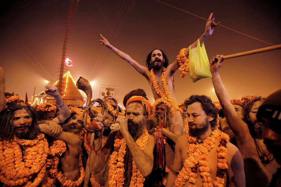 Naked Hindu holy men or a Naga Sadhus leave from their camp for a dip at Sangam, the confluence of the Rivers Ganges, Yamuna and mythical Saraswati on one of the most auspicious day Makar Sankranti,  the first day of the Maha Kumbh Mela, in Allahabad, India, Monday, Jan. 14, 2013. Millions of Hindu pilgrims are expected to take part in the large religious congregation of a period of over a month on the banks of Sangam during the Maha Kumbh Mela in January 2013, which falls every 12th year, where devotees wash themselves in the waters of the Ganges believing that it washes away their sins and ends the process of reincarnation. (AP Photo /Rajesh Kumar Singh) Photo: Rajesh Kumar Singh, ASSOCIATED PRESS / AP2013
