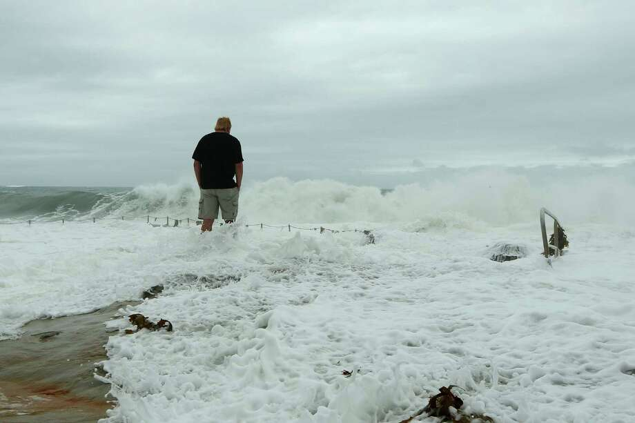 A man watches the large swell at the Dee Why baths Tuesday in Sydney.  Photo: Cassie Trotter, Getty / 2013 Getty Images