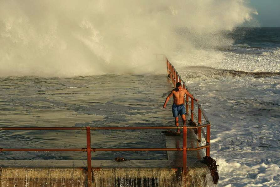 A man hangs onto the railing of North Curl Curl ocean pool.