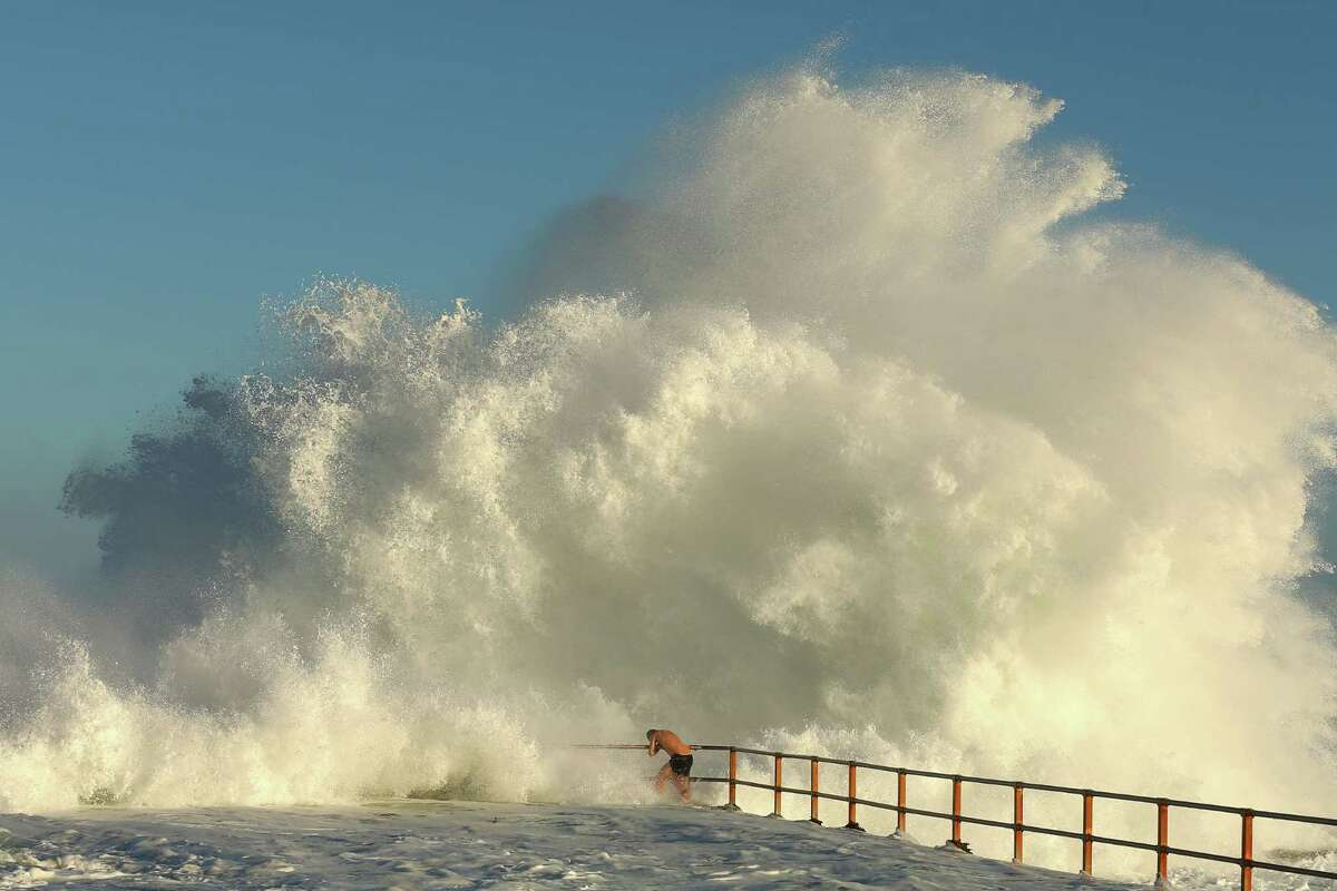 A man hangs onto the railing of North Curl Curl ocean pool Tuesday in Sydney.