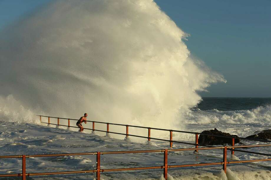 A man hangs onto the railing of North Curl Curl ocean pool Tuesday in Sydney.  Photo: Cameron Spencer, Getty / 2013 Getty Images