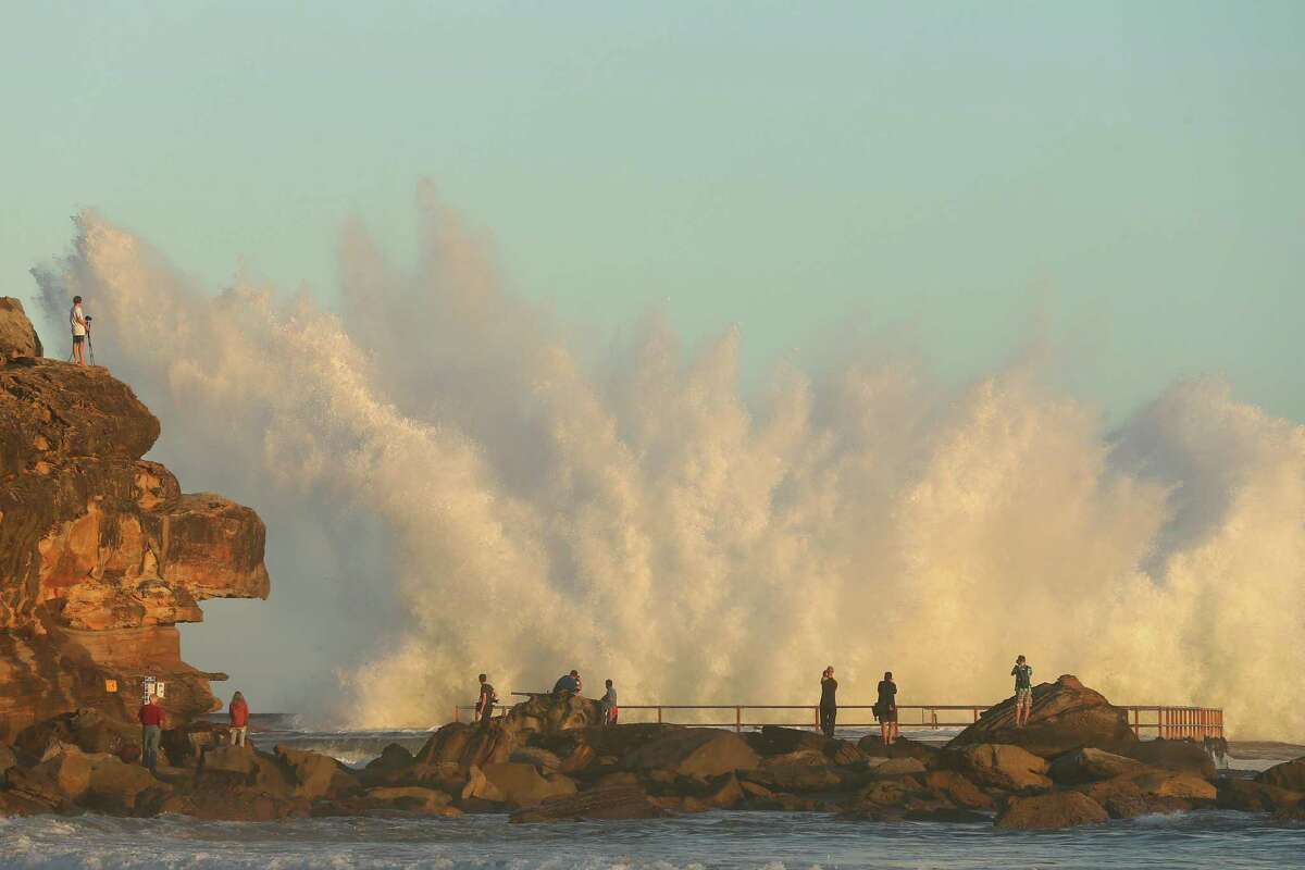 People gather to watch waves crash over North Curl Curl ocean pool after winds and rain battered Sydney producing large swells on Tuesday in Sydney, Australia. Parts of Sydney experienced record rainfall after ex-cyclone Oswald swept through the city Monday night.