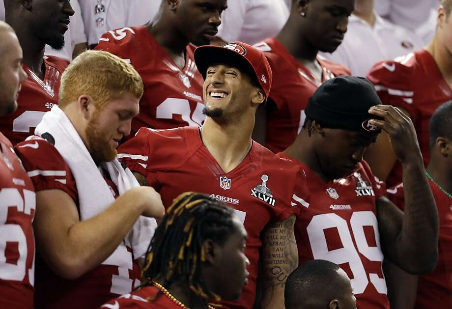 San Francisco 49ers quarterback Colin Kaepernick smiles as the team sets up for a photo during media day for the NFL Super Bowl XLVII football game Tuesday, Jan. 29, 2013, in New Orleans. Photo: Mark Humphrey, Associated Press