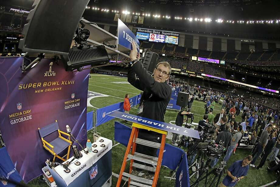 A member of the NFL media team switches the name signs from San Francisco 49ers head coach Jim Harbaugh to Baltimore Ravens head coach John Harbaugh during media day for the NFL Super Bowl XLVII football game Tuesday, Jan. 29, 2013, in New Orleans. (AP Photo/Charlie Riedel) Photo: Charlie Riedel, Associated Press